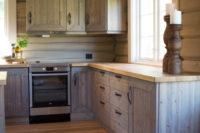 Skreddersydd kjøkken tilpasset et hjørne i en tømmerhytte.
